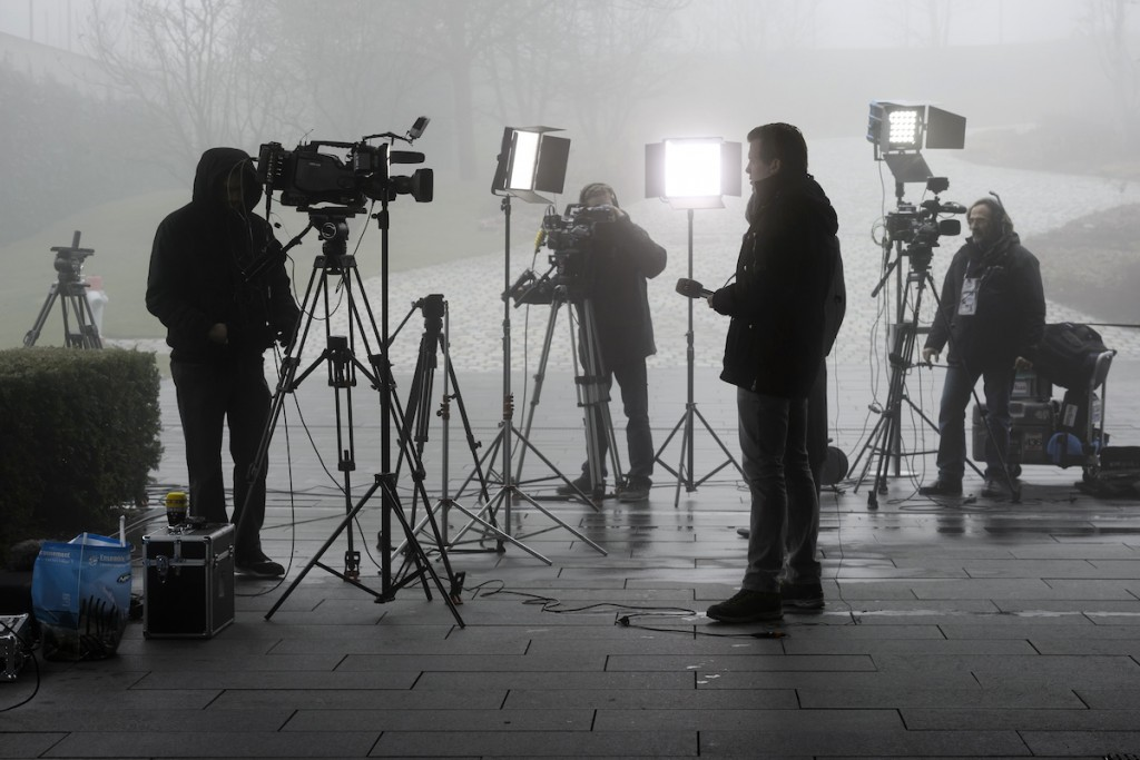 TV journalist operates at the FIFA headquarters engulfed by fog on December 3, 2015 in Zurich. In a dramatic widening of the FIFA corruption scandal, Swiss police arrested two more top football officials in a dawn raid Thursday on suspicion that they accepted millions of dollars in bribes. / AFP / FABRICE COFFRINI